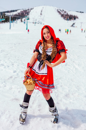 Beautiful young woman in a costume of Little Red Riding Hood with wicker basket and kruasan on the snowy winter slope