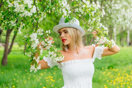 Modern bride in white cylinder hat enjoying blooming apple tree flowers