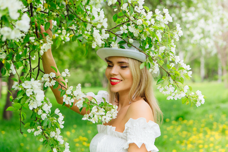 Sexy modern bride in white cylinder hat enjoing bloomin apple tree flowers