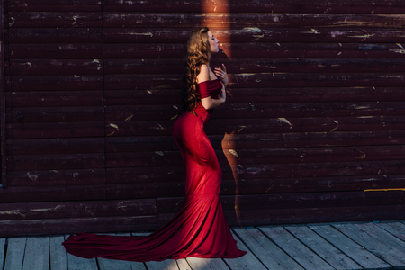 Back view of a beautiful young woman in a long red evening gown with a train standing and black hat next to the wooden wall in a ray of light. 版權商用圖片