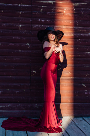 Back view of a beautiful young woman in a long red evening gown with a train standing and black hat next to the wooden wall in a ray of light. Фото со стока