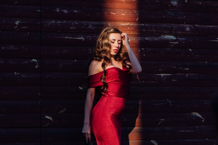 Back view of a beautiful young woman in a long red evening gown with a train standing and black hat next to the wooden wall in a ray of light. Stock fotó