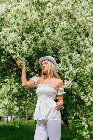 Sexy modern bride in white cylinder hat enjoing bloomin apple tree flowers in spring time
