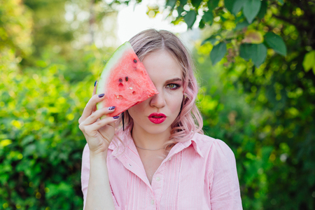 Beautiful young woman with pink hair holding a slice of sweet juicy watermelon in front of her face