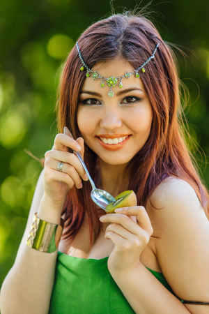 Portrait of a beautiful young asian woman in green dress and diadema on head eating kiwi
