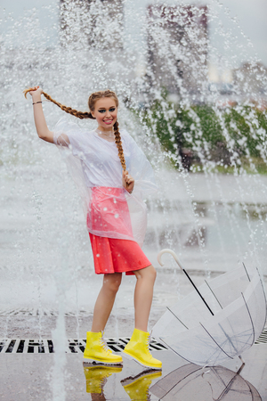 Young pretty girl with two braids in yellow boots and with transparent umbrella stands near fountain. Rainy day in city.