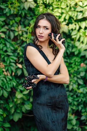 Portrait of young sexy brunette in black dress biting black grapes. Stock Photo