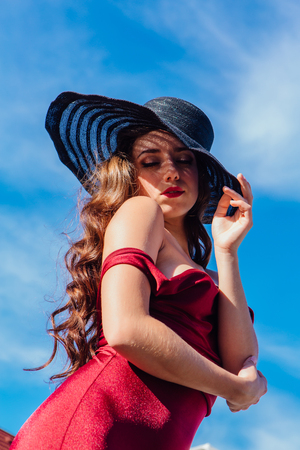 Beautiful young woman in red dress and balack hat in summer sunny day on the blue sky background. Retro fashion