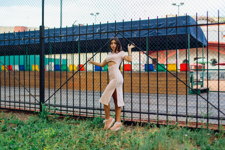 Portrait of a young brunette swag girl in pink sport dress standing next to the iron fence.