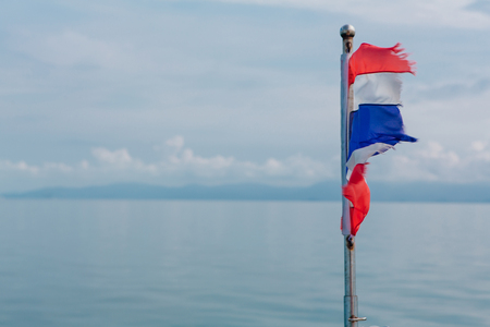 Thailand flag on the background of blue sea and cloudy sky surface. Flag on the wind.