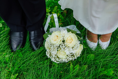 Feet of groom and bride with wedding bouquet standing close to each other on the green grass Stock Photo