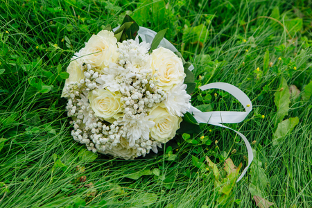 Beautiful wedding bouquet made with white roses on the green grass background.