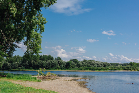 River coast with beach and cloudy sky at summer day