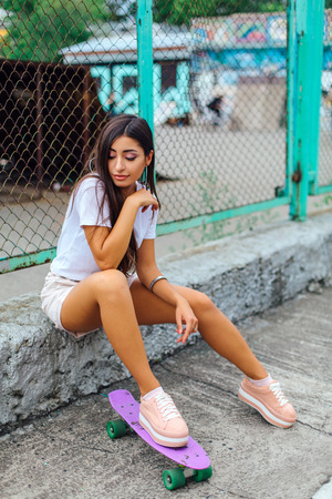 Summer lifestyle image of trendy pretty young girl sitting next to the skateboard coart with her purple plastic skateboard.