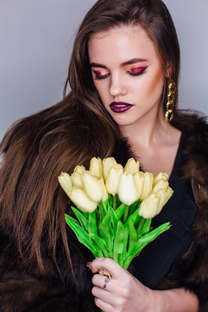 Beauty portrait of a woman with bright colorful make-up dressed in natural fur coat holding bouquet of yellow tulips