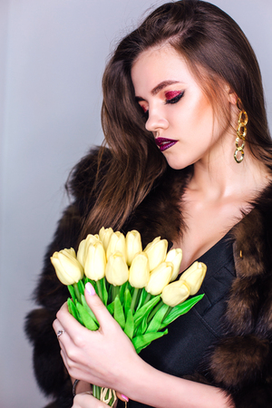 Beauty portrait of a woman with bright colorful make-up dressed in natural fur coat holding bouquet of yellow tulips Фото со стока - 122939360