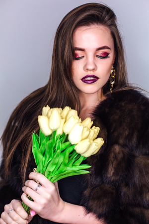 Beauty portrait of a woman with bright colorful make-up dressed in natural fur coat holding bouquet of yellow tulips Фото со стока - 122939362