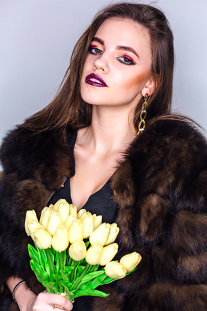 Beauty portrait of a woman with bright colorful make-up dressed in natural fur coat holding bouquet of yellow tulips Фото со стока - 122939364