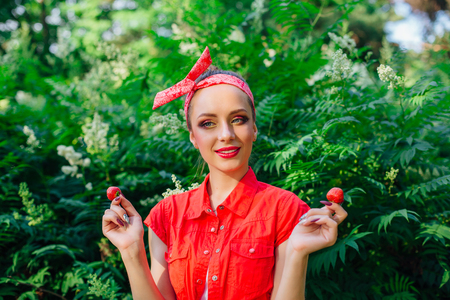 Beautiful young pin up girl dressed in red shirt with bright make up and fresh natural strawberry.