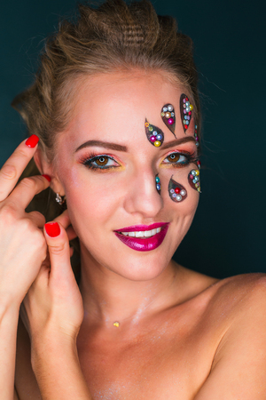 Beautiful young woman with flower face art. Spring makeup. Beauty fashion. Creative woman holiday make-up with sparles and decorative crystals