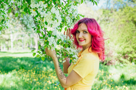 Beautiful and young woman with bright red hair and ref lips standing next to a blooming apple tree in a yellow dress. Spring portrait. Stok Fotoğraf