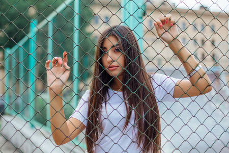 Portrait of a young brunette swag girl behind the rabitz fence. Reklamní fotografie