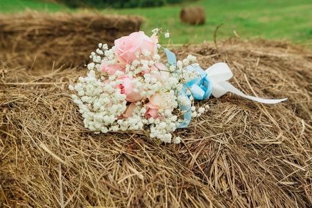 Wedding bouquet with pink roses laying at dry haystack