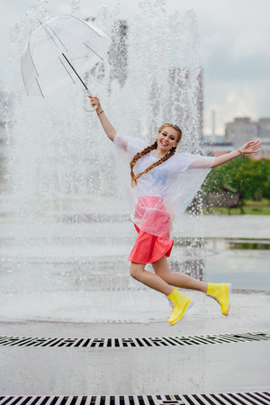 Young pretty girl with two braids in yellow boots and with transparent umbrella jumping near fountain. Rainy day in city.