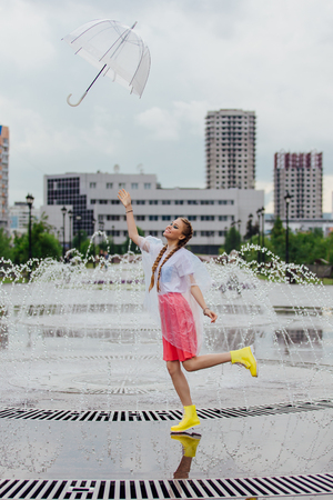 Young pretty girl with two braids in yellow boots throwing and catching transparent umbrella near fountain. Rainy day in city.