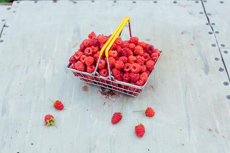 Mini shopping basket full of fresh red ripe raspberry on old grey vintage background in garden Stock Photo