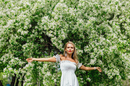 Sexy modern bride enjoing blooming apple tree flowers in spring time Фото со стока - 122939500