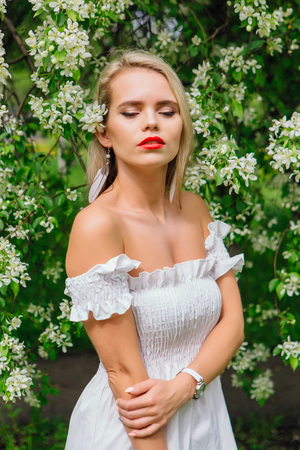 Sexy modern bride enjoing blooming apple tree flowers in spring time Фото со стока - 122939608