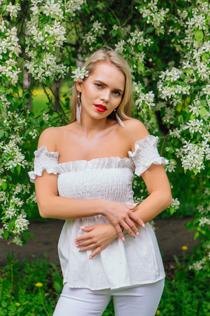 Sexy modern bride enjoing blooming apple tree flowers in spring time Фото со стока