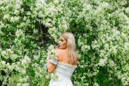 Sexy modern bride enjoing blooming apple tree flowers in spring time Фото со стока - 122939615