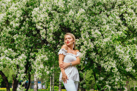 Sexy modern bride enjoing blooming apple tree flowers in spring time Фото со стока - 122939820