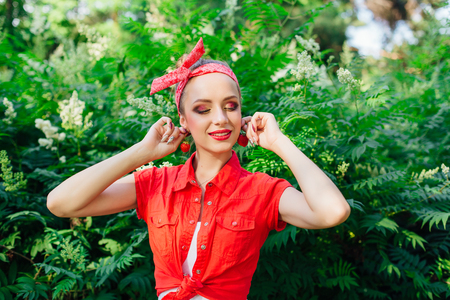 Beautiful young pin up girl dressed in red shirt with bright make up and fresh natural strawberry. Фото со стока - 122939821