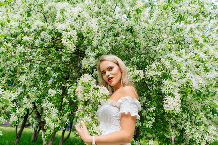 Sexy modern bride enjoing blooming apple tree flowers in spring time Фото со стока - 122939827