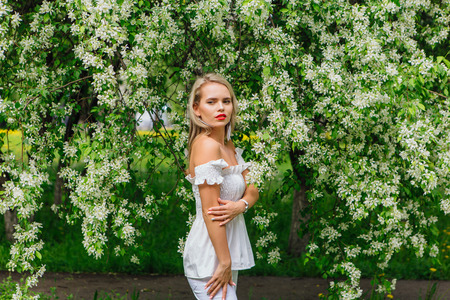 Sexy modern bride enjoing blooming apple tree flowers in spring time Фото со стока - 122939830
