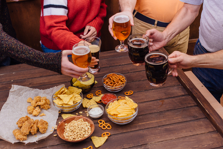 Hands of friends holding beer glasses drinking together in the pub Stok Fotoğraf