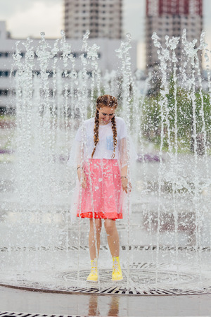 Young wet pretty girl with two braids in yellow boots stands inside of fountain. Rainy day in city.