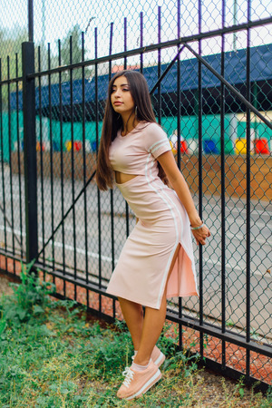 Portrait of a young brunette swag girl in pink sport dress standing next to the iron fence. Фото со стока - 122939922