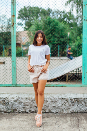 Portrait of a young brunette swag girl standing next to rabitz fence. Фото со стока - 122939923