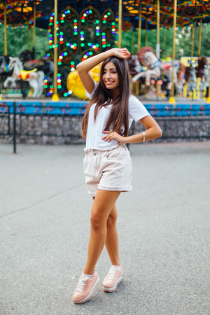Portrait of a young brunette swag girl standing next to carousel in park. Фото со стока