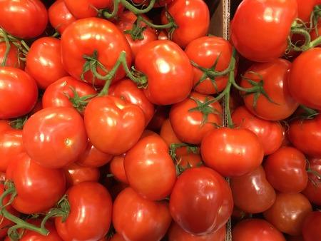 Tomates rojos sabrosos con hojas verdes en la caja en el mercado Foto de archivo