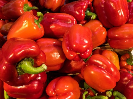 Red bell peppers on market: close up filling the whole photo. Sweet peppers, paprika. Stock Photo