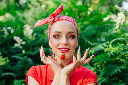 Beautiful young pin up girl dressed in red shirt with bright make up and fresh natural strawberry. Imagens
