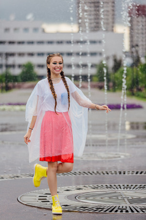 Young wet pretty girl with two braids in yellow boots and with transparent umbrella stands inside of fountain. Rainy day in city. Фото со стока - 122940025