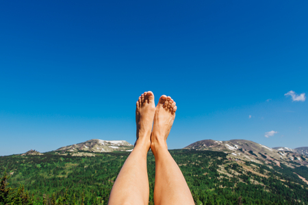 Female feet up infront of the clear blue sky and mountains