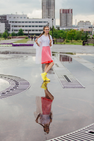 Young wet pretty girl with two braids in yellow boots stands near fountain. Rainy day in city. Young girl reflecting in the wet ground