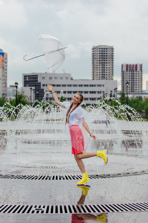 Young pretty girl with two braids in yellow boots throwing and catching transparent umbrella near fountain. Rainy day in city. Фото со стока